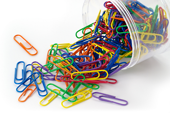 Colored paper clips spilt from a battered plastic container